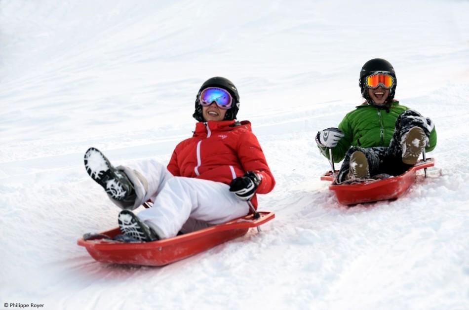 Deux adultes aux sports d'hiver utilisant la luge de glisse