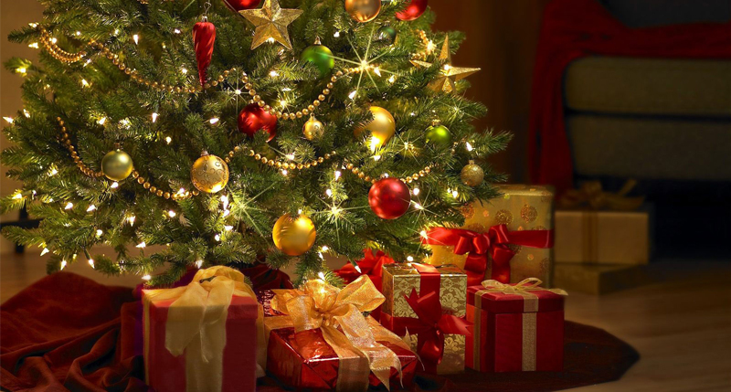 Sapin de Noël éclairé avec quelques cadeaux.