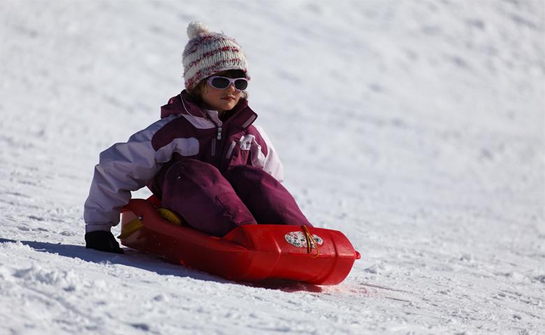 Enfant descendant une piste enneigée sur une luge.